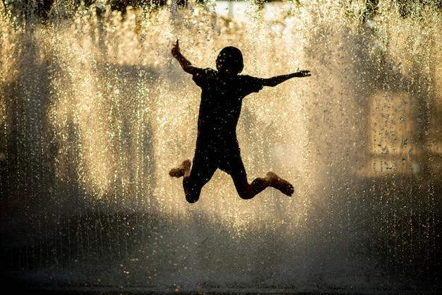 Der kleine junge, der wasser spielt, lässt brunnen unter dem stoff und dem regenschirm fallen Premium Fotos