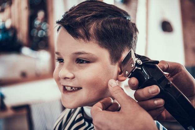 Der kleine junge lächelt, als seine haare geschnitten werden. Premium Fotos