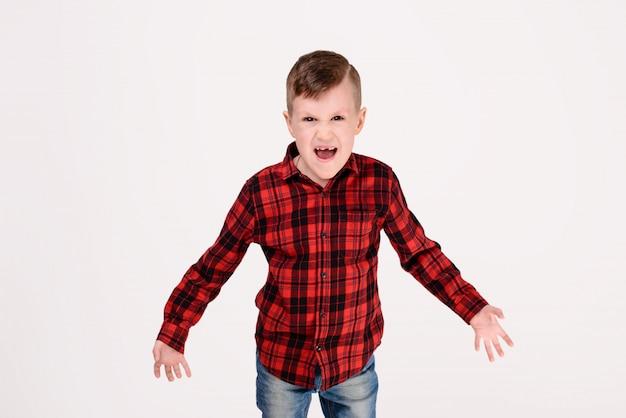 Der kleine junge mit ausdrucksvollem gefühl auf einem weißen hintergrund. Premium Fotos
