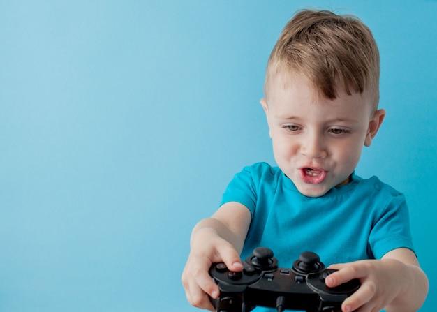 Der kleinkindjunge, der blaue kleidung trägt, halten in der hand steuerknüppel für spiele, kinderstudioporträt. leutekindheits-lebensstilkonzept. mock up kopie raum Premium Fotos