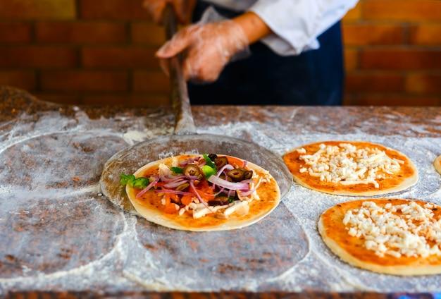 Der koch legt die pizza in den ofen. Premium Fotos