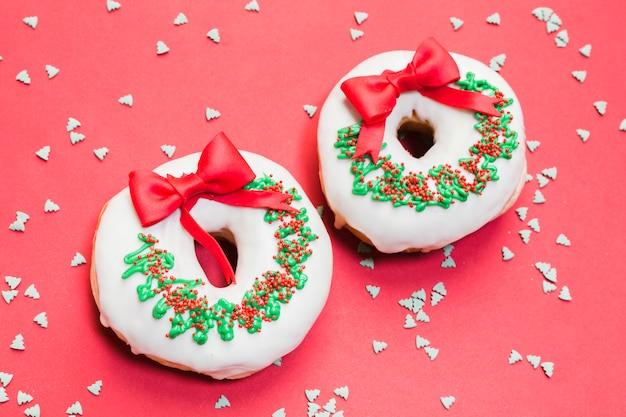 Der köstliche donut, der für weihnachten auf rotem hintergrund mit verziert wird, besprüht Kostenlose Fotos