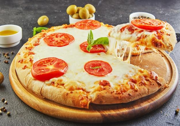 Der köstliche geschmack von pizza und käsescheiben mit mozzarella und tomaten. dreieckspizza mit stretchkäse und gewürzen Premium Fotos