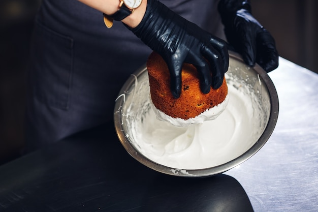 Der konditor taucht die oberseite des osterkuchens in eine proteincreme. Premium Fotos