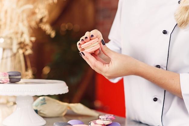 Der konditor verbindet die teile der macarons mit einer creme miteinander. schließen sie herauf bäckerhände, die macarons machen. Premium Fotos