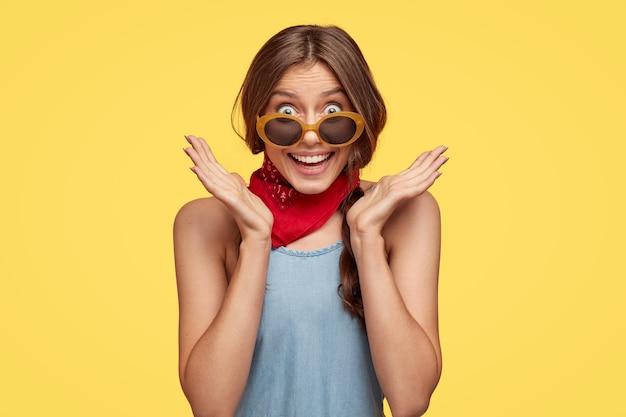 Der kopfschuss einer verblüfften fröhlichen europäischen frau breitet die hände in der nähe des gesichts aus, lächelt breit, bemerkt etwas angenehmes, trägt eine trendige sonnenbrille, isoliert über der gelben wand, drückt positivität aus Kostenlose Fotos