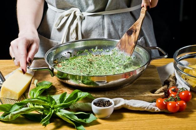 Der küchenchef bereitet eine sauce aus spinat und sahne, penne pasta. Premium Fotos