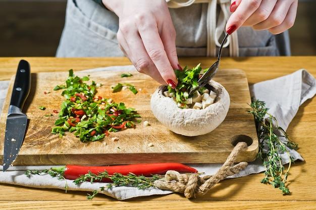 Der küchenchef bereitet gefüllte champignons zu Premium Fotos