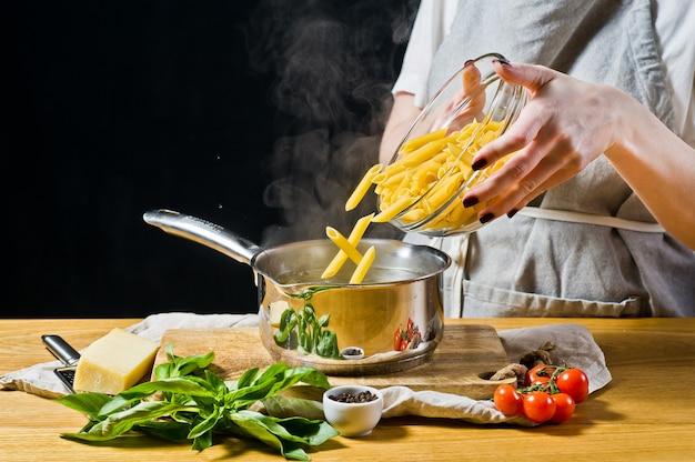Der küchenchef gießt die pasta penne in einen topf mit kochendem wasser. Premium Fotos