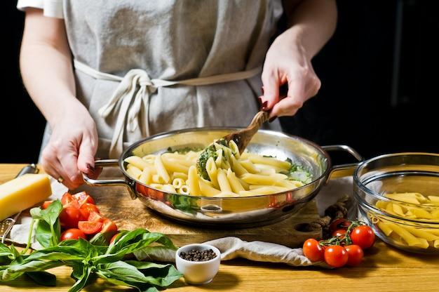 Der küchenchef kocht nudeln penne mit spinat. Premium Fotos