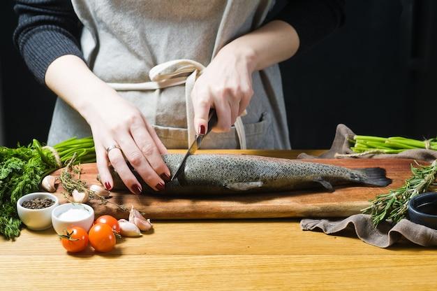 Der küchenchef schneidet rohe forellen auf einem hölzernen schneidebrett. Premium Fotos