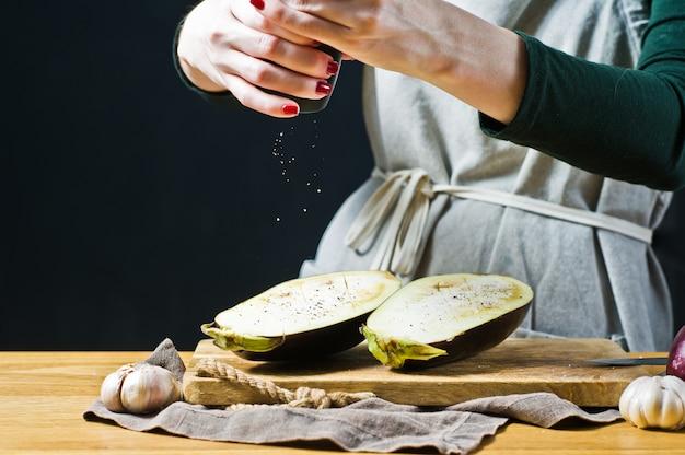 Der küchenchef streut salz auf die gegrillte aubergine seitenansicht, platz für text Premium Fotos
