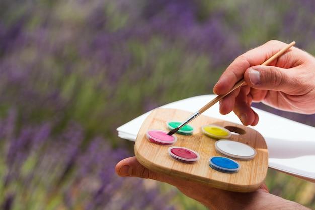 Der künstler hält in seinen händen eine palette mit farben und eine wickelzeichnung auf einem blatt papier Premium Fotos