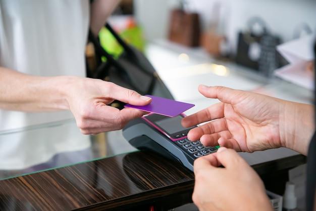Der kunde gibt dem kassierer über dem schreibtisch eine kreditkarte mit pos-terminal zur zahlung. kurzer schuss, nahaufnahme der hände. einkaufskonzept Kostenlose Fotos