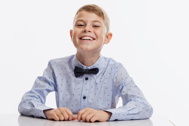 Der lachende schüler in einem blauen hemd mit einer fliege