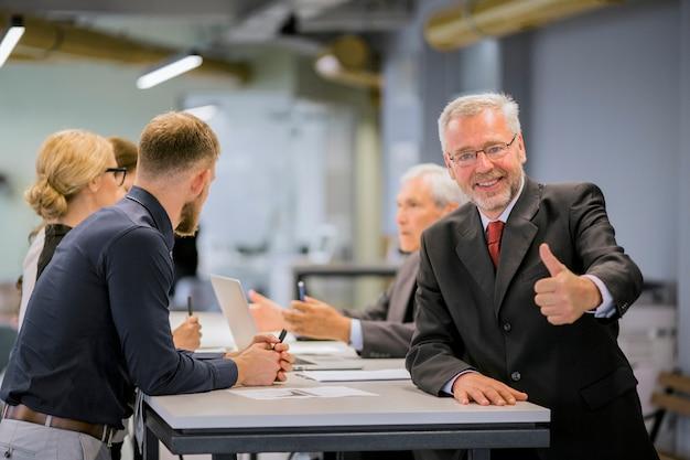 Der lächelnde ältere geschäftsmann, der daumen herauf zeichen vor den wirtschaftlern sich besprechen im büro zeigt Kostenlose Fotos