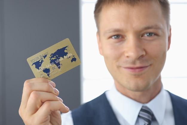 Der lächelnde geschäftsmann hält eine plastikbankkarte in der hand Premium Fotos