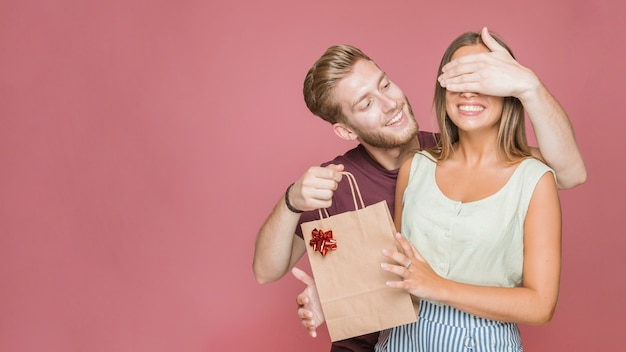 Der lächelnde junge mann, der ihre freundinnen bedeckt, mustert, einkaufstasche halten Kostenlose Fotos