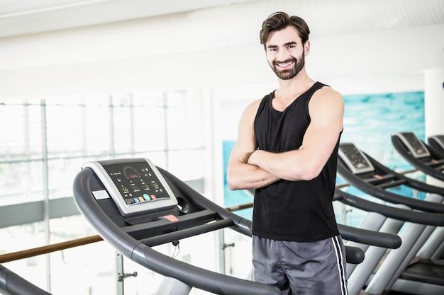 Der lächelnde mann, der auf tretmühle mit den armen steht, kreuzte an der turnhalle Premium Fotos