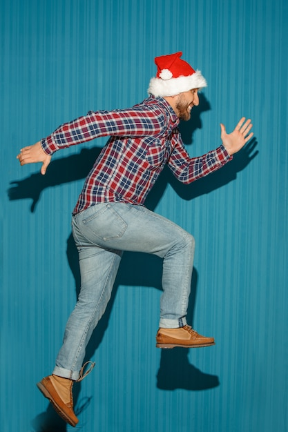 Der laufende weihnachtsmann, der eine weihnachtsmütze trägt Kostenlose Fotos