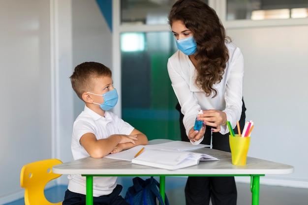 Der lehrer erklärt einem schüler, wie wichtig die desinfektion ist Kostenlose Fotos