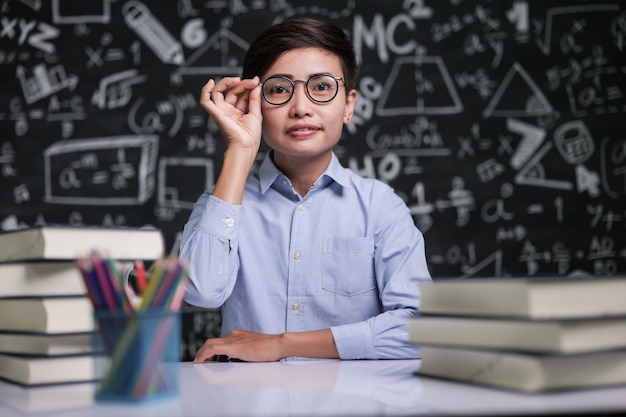 Der lehrer saß am tisch und hielt die brille im klassenzimmer. Kostenlose Fotos
