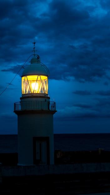 Der leuchtturm leuchtet in der dunklen nacht an der küste spaniens Premium Fotos