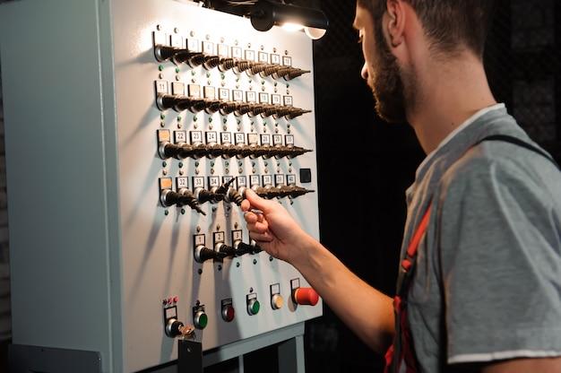 Der lichttechniker stellt die lichter auf der bühne in der nähe der szenen ein Premium Fotos