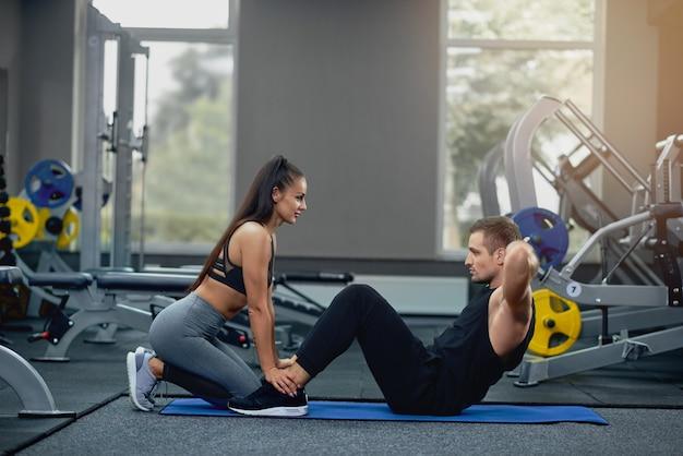Der mann, der abdominal- krisen tut, drücken übung mit weiblichem persönlichem trainer. Premium Fotos