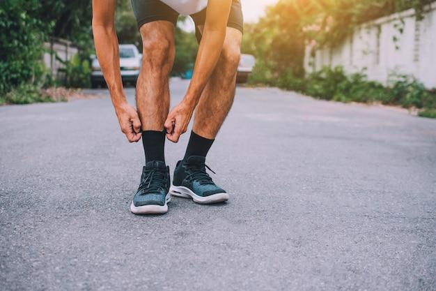 Der mann, der auf der straße läuft, läuft für übung, lässt sport und nahaufnahme am laufschuh laufen Premium Fotos