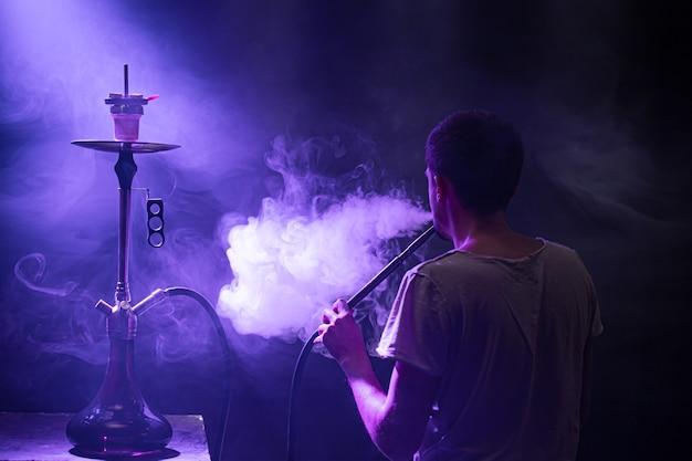 Der mann, der die klassische shisha raucht. schöne farbige licht- und rauchstrahlen. das konzept des shisha-rauchens. Kostenlose Fotos