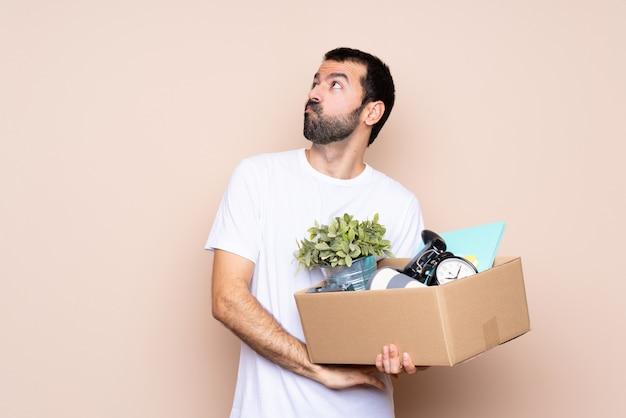 Der mann, der einen kasten hält und in das neue haus umzieht, das zweifel macht, gestikulieren beim anheben der schultern Premium Fotos