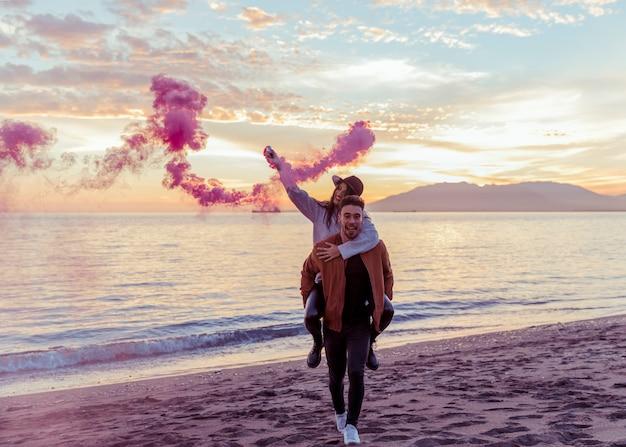 Der mann, der frau mit rosa rauchbombe hält, ziehen an sich auf seeufer zurück Kostenlose Fotos