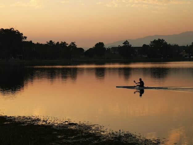 Der mann, der kajak trainiert, segelt im flusssonnenuntergang Premium Fotos