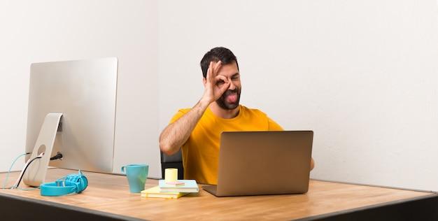 Der mann, der mit laptot in einem büro arbeitet, macht lustiges und verrücktes gesichtsgefühl Premium Fotos
