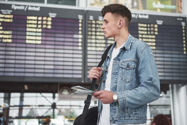 Der mann erwartet seinen flug am flughafen. Kostenlose Fotos