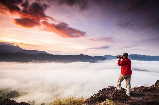Der mann fotografiert das nebelmeer auf dem hohen berg. Premium Fotos