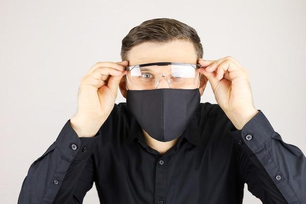 Der mann im schwarzen hemd trug eine medizinische brille auf weißem grund Premium Fotos