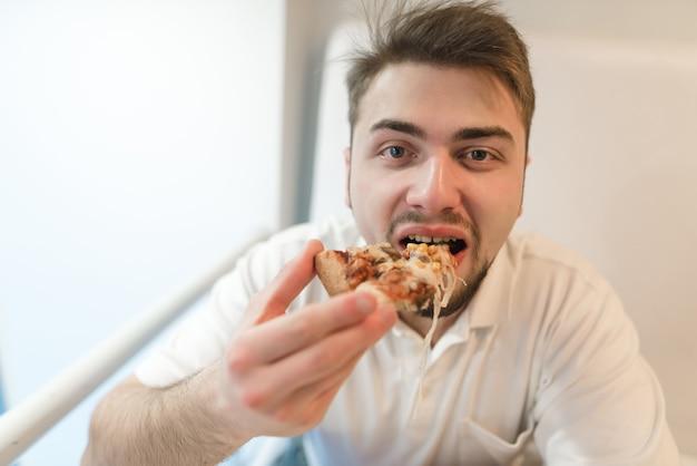 Der mann isst eine leckere pizza. fast food zum mittagessen. Premium Fotos