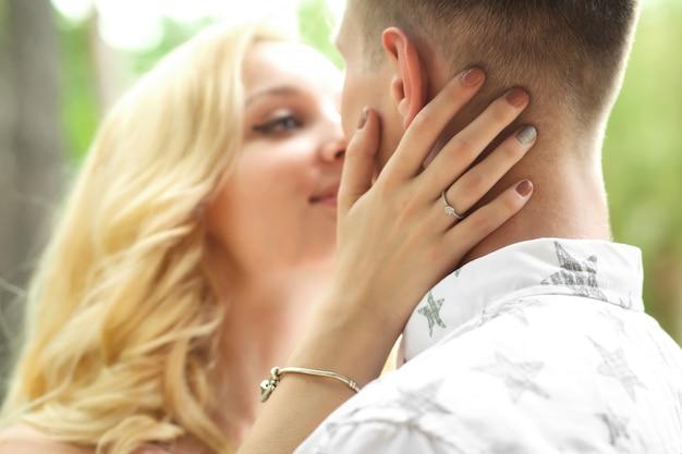 Der mann mit der frau umarmt und küsst sich. ein romantisches date in einem pinienwald, liebespaar eines schönen paares Premium Fotos