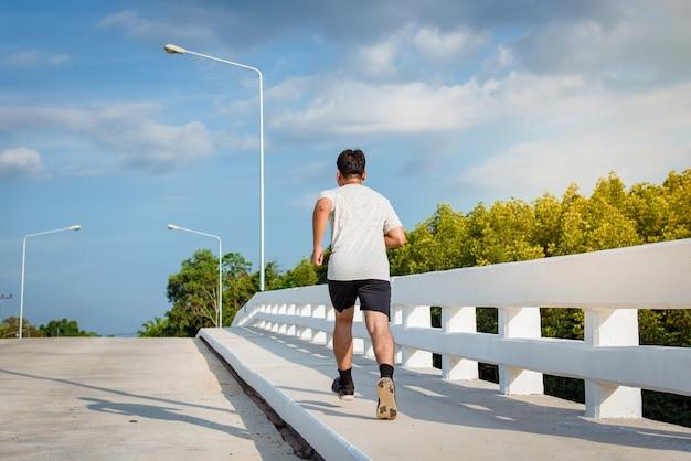 Der mann mit läufer auf der straße an der brücke läuft für übung Premium Fotos