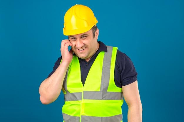 Der mann mittleren alters des konstrukteurs, der gelbe weste der konstruktion und sicherheitshelmkratzgesicht trägt, das etwas schlau schlaues schema entwirft, haben interessante idee über isolierter blauer wand Kostenlose Fotos