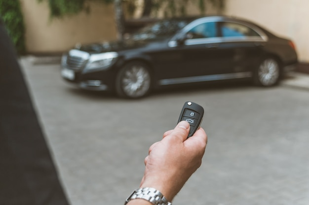 Der mann öffnet das auto mit einem schlüsselbund, im hintergrund ein schwarzes auto. Premium Fotos