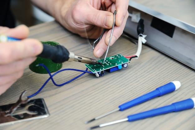 Der mann repariert die stromversorgung der lampe. er hält eine elektronische platine und einen lötkolben in der hand. Premium Fotos