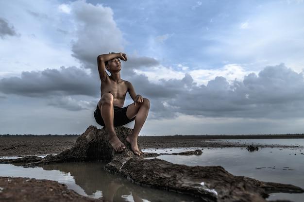 Der mann saß auf der basis des baumes, die hand auf die stirn gelegt und von wasser umgeben. Kostenlose Fotos