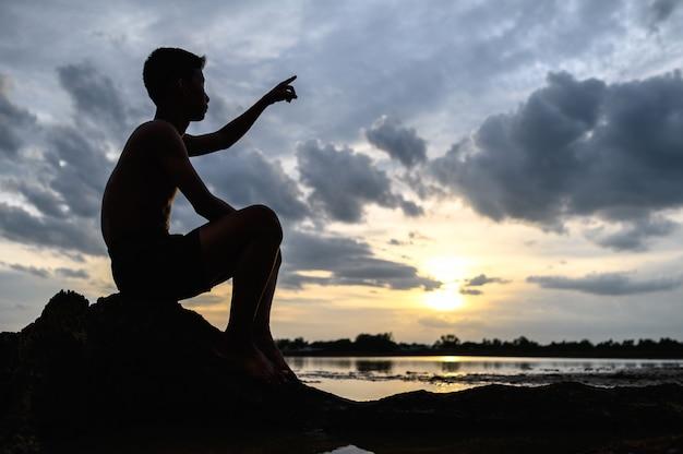 Der mann saß auf der basis des baumes und zeigte mit den händen nach vorne während des sonnenuntergangs. Kostenlose Fotos