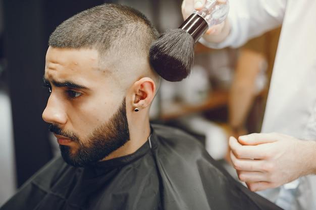 Der mann schneidet seinen bart in den friseursalon. Kostenlose Fotos