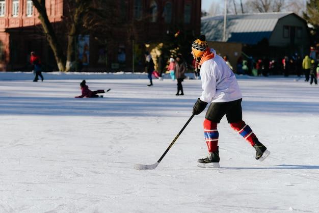 Der mann spielt hockey auf der eisbahn Premium Fotos