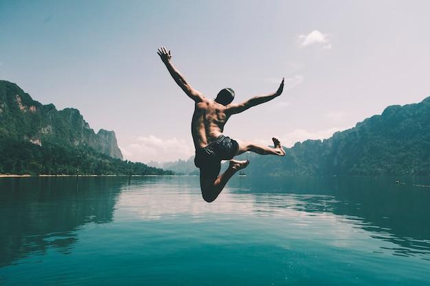 Der mann springend mit freude an einem see Kostenlose Fotos
