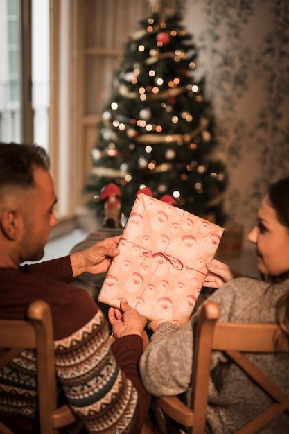 Der mann und frau, die präsentkarton auf stühlen halten, nähern sich weihnachtsbaum Kostenlose Fotos